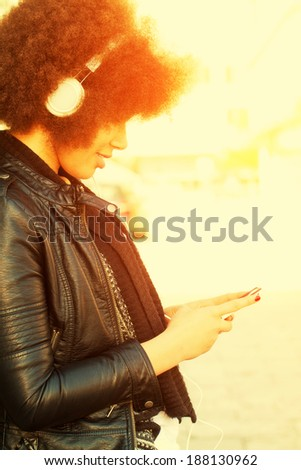 Girl listen music in the sun - stock photo