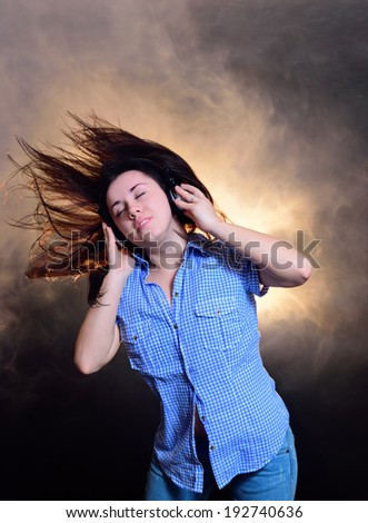Girl listening to music and dancing in the smoke