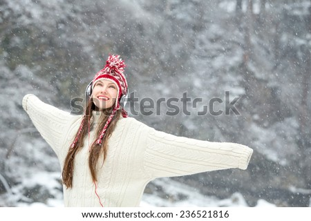 girl listening to music. Emotional portrait of happy woman in winter landscape - stock photo