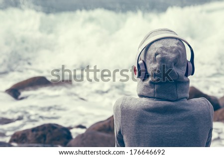 girl listening to music on the seafront - stock photo