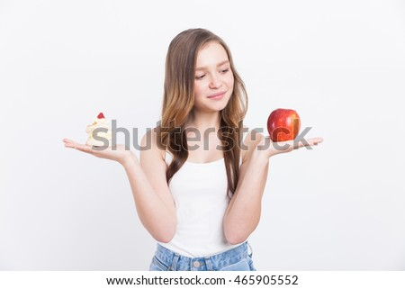 Girl looking at apple and deciding to eat it before cupcake. Concept of little pleasures