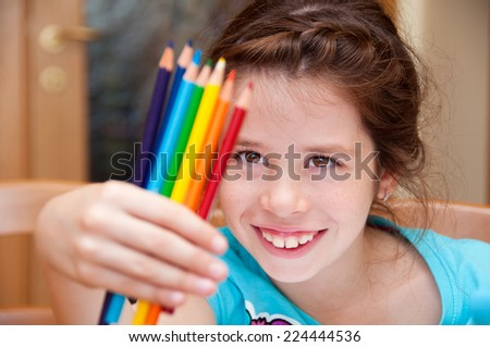 Girl looking at color pencils - stock photo