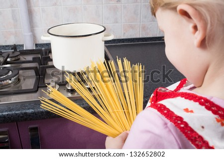 girl looking at pasta in the kitchen - stock photo