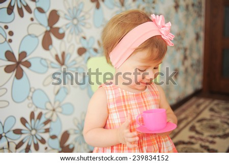 girl looking at pink cup with saucer - stock photo