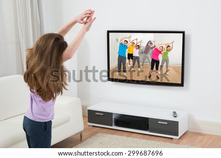 Girl Looking At Television While Doing Exercise At Home - stock photo