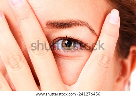girl looking between her fingers - stock photo