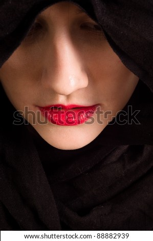Girl looking down with black hood - stock photo