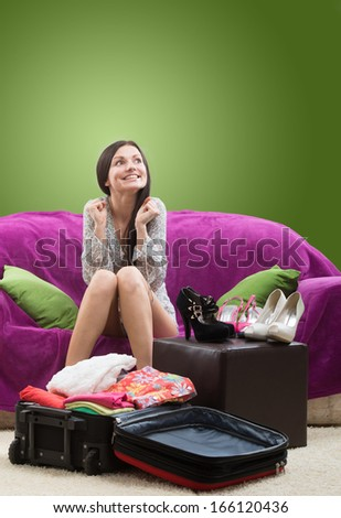 Girl looking forward to her vacation, studio shot on green background - stock photo