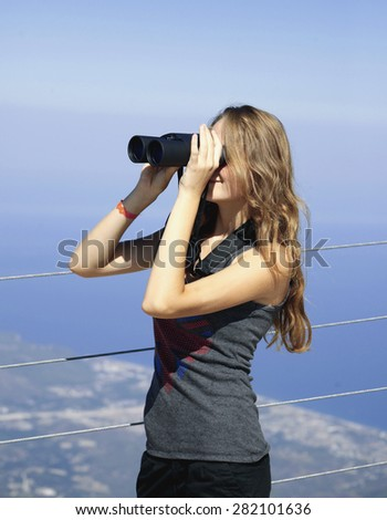 Girl looking in binoculars enjoying spectacular view on mountain top above the clouds - stock photo