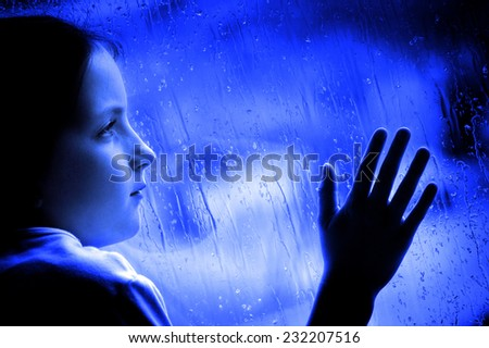 Girl looking out window on rainy day sad depressed feeling lonely - stock photo