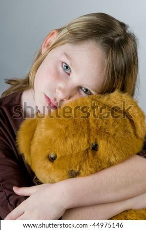 Girl looking sad hugging bear - stock photo