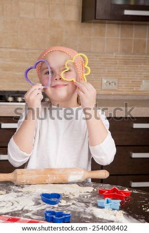 girl looking through a cookie cooking mold of the heart and smiling - stock photo