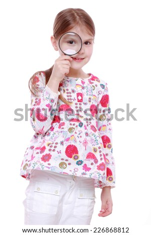 girl looking through magnifying glass isolated over white background - stock photo