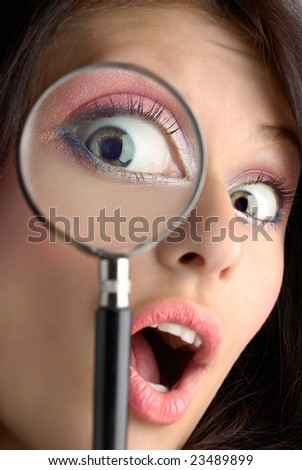 Girl looking through the magnifying glass - stock photo