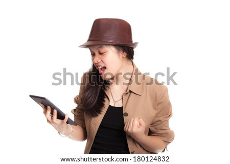 Girl looking to tablet in her hand with surprise - stock photo