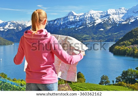 Girl looking to the map. Switzerland - stock photo