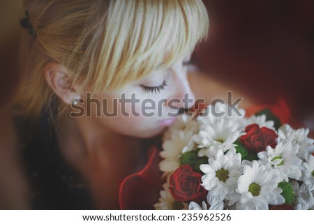 Girl looks at a bouquet of roses and daisies