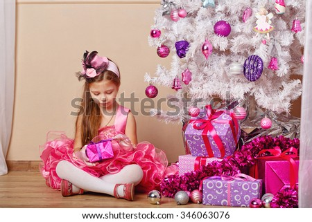 Girl looks at a gift. Child wearing a dress and sitting next to the Christmas tree. New Year. Holiday and fun. Merry Christmas. 2017 - stock photo