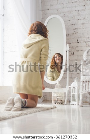 girl looks at herself in the mirror. Cute  girl looks at herself in the mirror, light room. Girl in knitted sweater winter morning, looks in the mirror  - stock photo