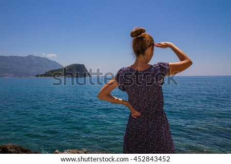 Girl looks for something in the sea, closeup, one hand at the forehead, the other on the waist/ A young girl looks into the distance/ Waiting on the sea