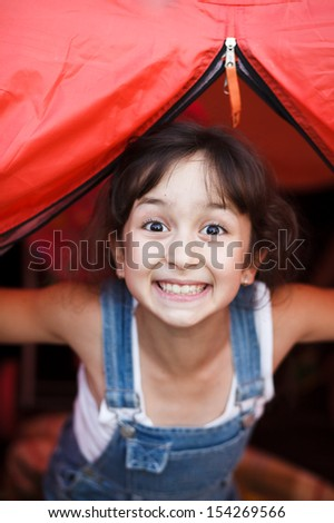 Girl  looks out from a tent