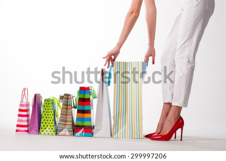 Girl looks  the purchases on a white background. Girl in red shoes.