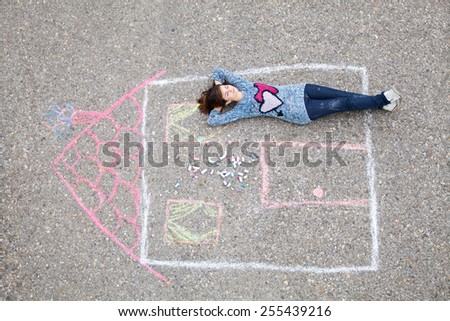 Girl lying in a drawn house - stock photo