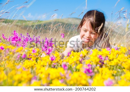 Girl lying in a field of wild flowers - stock photo