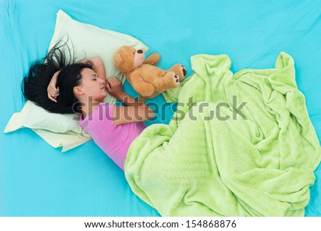 Girl lying in bed and sleeping on her side, view from above - stock photo