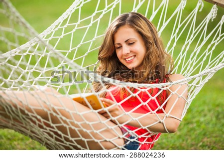 Girl lying in hammock and reading a book - stock photo