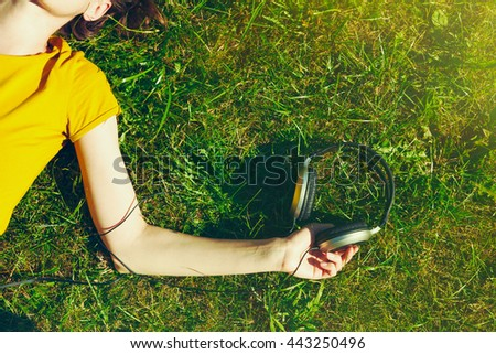 girl lying in summer grass with headphones listening to music and relaxing