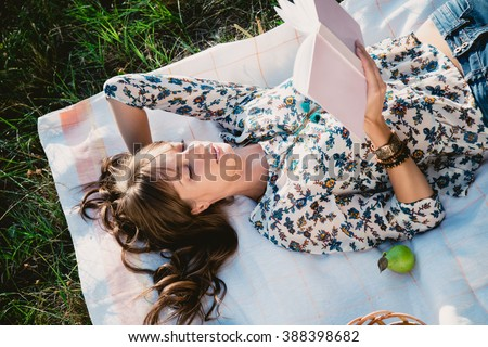 Girl lying in the park and reading a book - stock photo