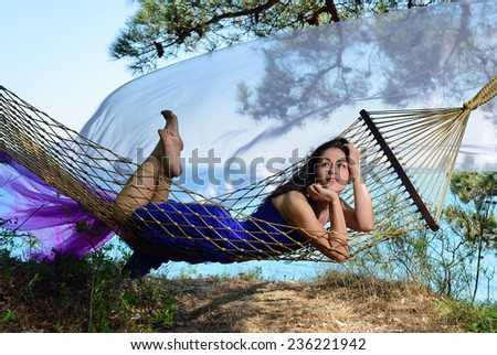 Girl lying on a hammock on a sea background  - stock photo