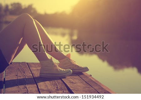Girl lying on a pier - stock photo