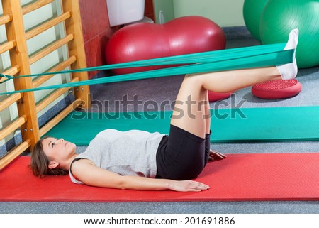 Girl lying on exercise mat and stretching legs with elastic band - stock photo
