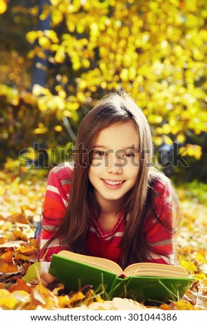 girl lying on fallen leaves  in the park and reading a book. reading, learning and education in autumn