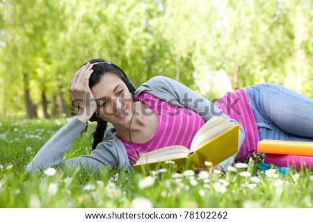 girl lying on grass with flower in park, reading  book and listening music through headset - stock photo