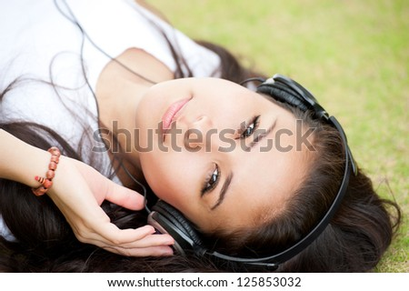 Girl lying on grass with headphones and looking at camera