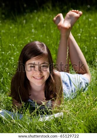 Girl lying on green meadow reading book - stock photo