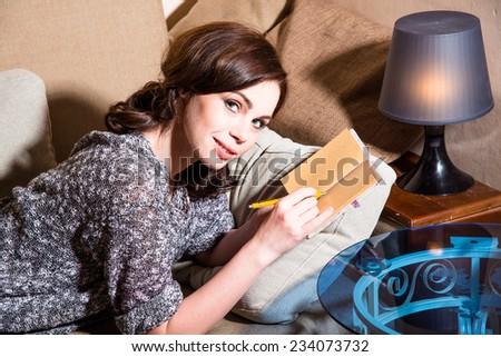 Girl lying on the couch and reading a book - stock photo
