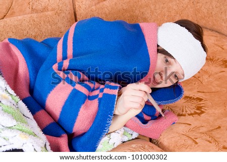 girl lying on the couch sick with a thermometer - stock photo