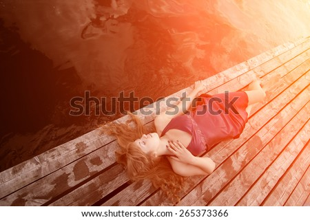 Girl lying on the wooden floor in the sunlight. Beautiful young woman on sunset light. Hipster, youth lifestyle Backlit and toned. sunshine glow sun, sunbeams Enjoying nature outdoor. Freedom concept - stock photo