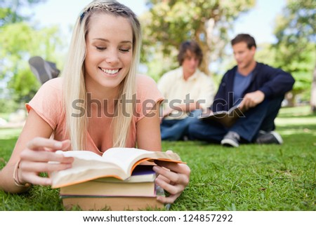 Girl lying while reading books in a park with friends in background - stock photo