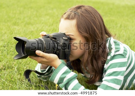 Girl lying with photo camera on grass