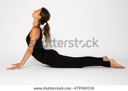 Girl makes yoga exercise on the white background