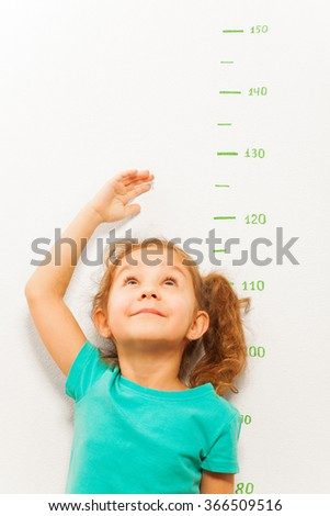 Girl measure height with hand looking up - stock photo