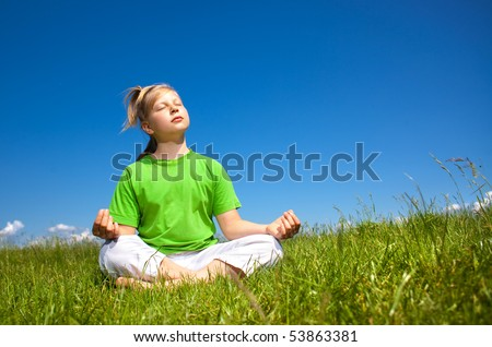 Girl meditates in a field