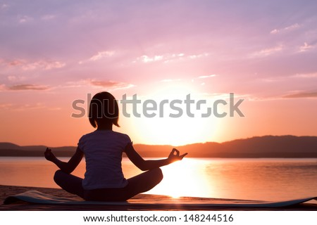 Girl meditating at sunrise on the beach - stock photo