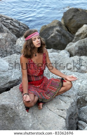 Girl meditating on the rock - stock photo