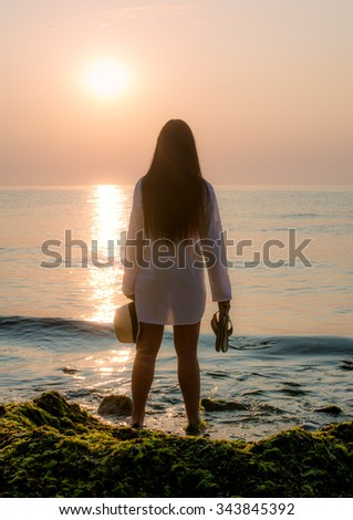 girl meets sunrise on seaside - stock photo